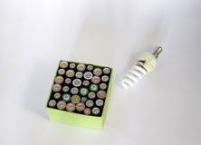Used rechargeable batteries and and economic bulb on white background Royalty Free Stock Photos