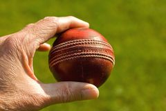 Used red leather cricket ball. Being held by hand against a green grass background stock photography