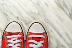 Used red sportshoes on marble background. Used red sportshoes on a marble background Stock Photo
