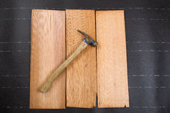 Used roofing hammer with new cedar wood shingles on felt paper Stock Photo
