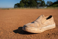 Used shoe dirt gravel alone discarded Royalty Free Stock Image