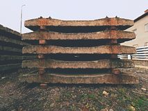 Used sleepers stock in railway depot. Old, dirty and rusty used concrete railway ties stored Stock Image
