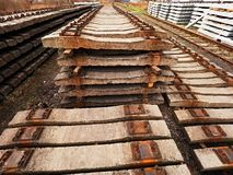 Used sleepers stock in railway depot. Old, dirty and rusty used concrete railway ties stored Royalty Free Stock Image