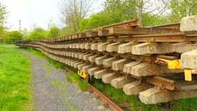 Used sleepers stock on wagon in depot. Old, dirty and rusty used concrete and wooden railway ties stored after reconstruction. Of railway station. Rails will stock video