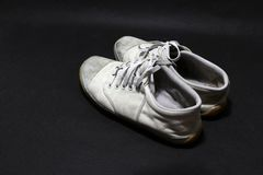Used sneakers shoes in white color but it grimy and Gloomy color, put pair on black floor. Royalty Free Stock Photography