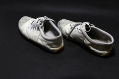Used sneakers shoes in white color but it grimy and Gloomy color, put pair on black floor. royalty free stock photo