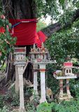 Used spirit House from people house dropped under the big sacred fig tree. stock photos