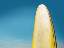 Used surf board against a bright blue sky with cle Royalty Free Stock Photo