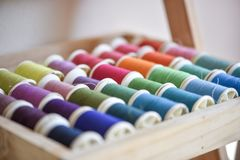 Colorful threads in wood box shot with macro lens. Used threads for sewing cloths are shot to show colors and textures in natural light Stock Image