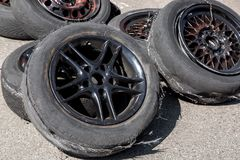 Used tire after drift. Stack up of used tires after drift racing, spoiled tire on black cast wheels Royalty Free Stock Images