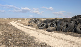 Used Tires in a Recycling Yard. Old used rubber tires piled in a recycling yard waiting to be shredded and remanufactured in to usable products stock photo