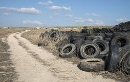 Used Tires in a Recycling Yard. Old used rubber tires piled in a recycling yard waiting to be shredded and remanufactured into usable products royalty free stock photo