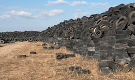 Used Tires in a Recycling Yard. Old used rubber tires piled in a recycling yard waiting to be shredded and remanufactured into usable products stock photography