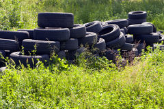 Used tires thrown in nature. Car tires pollute the environment Stock Photo