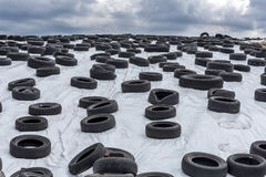 Used tires on a white hill under storm clouds Royalty Free Stock Photos