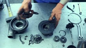 Used turbocharger. Car mechanic hands in garage with old and used turbocharger. Turbine Concept stock video footage