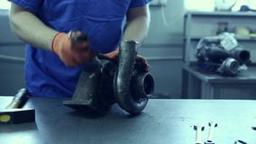 Used turbocharger. Car mechanic hands in garage with old and used turbocharger. Turbine Concept stock video