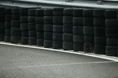 Used tyres used as guard rail on race circuit. Stacked rubber tyres used on the side of a tarmac circuit curve as guard rail safety road protection royalty free stock photography