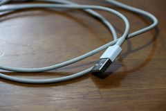 Used USB plug with cable on the wooden floor. stock photography