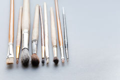 Used, vintage paintbrushes on gray background. macro view different size wooden and textured paint brush, shallow depth Royalty Free Stock Photography