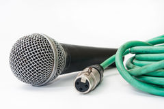 Used vocal microphone with old green xlr cable on the white back Royalty Free Stock Image
