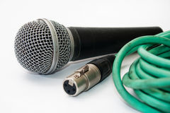Used vocal microphone with old green xlr cable on the white back Royalty Free Stock Photography