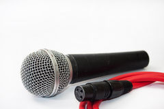 Used vocal microphone with red xlr cable on the white background Royalty Free Stock Photo