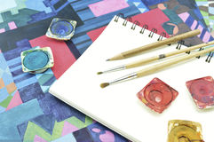 Used water color paint, pencil and paintbrush on white book Royalty Free Stock Photo