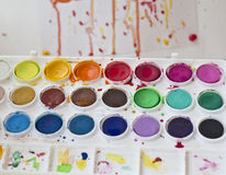 Used watercolor paint set. Used palette of multicolor watercolor paints with blurred drawing in the background Royalty Free Stock Photo