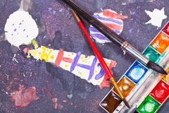 Used watercolor set and two old brushes on children picture Royalty Free Stock Photography