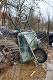 Used wheelbarrow construction cart leaning against wire fence. Used wheelbarrow construction cart with two handles and single wheel leaning against wire fence Royalty Free Stock Photos