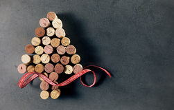 Used wine bottle cork Christmas Tree. A Christmas tree made of used wine bottle corks with a red decorative ribbon,  on a dark background with copy space Stock Image