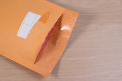 Used yellow blank envelope with transparent bubble wrap or packaging shockproof on wooden table. Stock Images