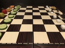 Free Useful And Harmful Foods Play Chess. Junk Foods Vs Vegetables Stock Images - 107362814