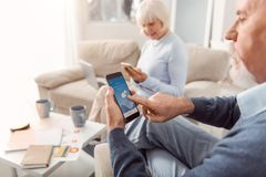 Pleasant elderly man checking weather forecast in mobile app. Useful app. The focus being on a bearded elderly men sitting in the armchair in the living room and stock image