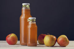 Useful apple juice with apples around on wooden table Royalty Free Stock Photo