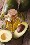Useful avocado oil in a bottle on a wooden table close-up, vertical Royalty Free Stock Photography