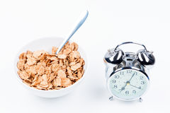 Useful breakfast of cereal and alarm clock on white table Royalty Free Stock Photos
