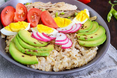 Useful breakfast: oatmeal with rabbit meat, avocado, boiled egg, tomatoes, radish. Green peas, flax seeds. Proper nutrition Stock Images