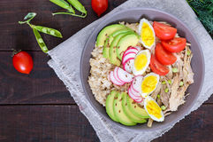 Useful breakfast: oatmeal with rabbit meat, avocado, boiled egg, tomatoes Royalty Free Stock Photo