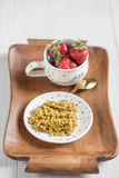 A useful breakfast on a tray, buckwheat porridge and ripe red st. Rawberries in a cup on a light wooden background Stock Image