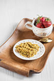 Useful breakfast on a tray, buckwheat porridge and ripe red stra. A useful breakfast on a tray, buckwheat porridge and ripe red strawberries in a cup on a light Royalty Free Stock Photos