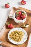 Useful breakfast on a tray, buckwheat porridge and ripe red stra. A useful breakfast on a tray, buckwheat porridge and ripe red strawberries in a cup on a light Stock Photos