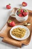 Useful breakfast on a tray, buckwheat porridge and ripe red stra. A useful breakfast on a tray, buckwheat porridge and ripe red strawberries in a cup on a light Royalty Free Stock Photo