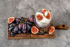 An useful dessert - yogurt, muesli and figs with grapes. On grey concrete background Stock Photo