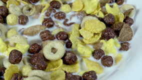 Useful Eating Habits. Plate with milk and mix of different types of breakfast cereal rotates slowly stock video footage
