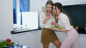 Useful food, cheerful girlfriends watch photos on android during lunch in kitchen. At weekend stock footage