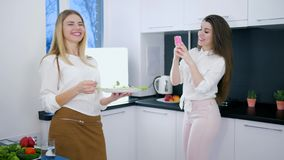 Useful food, pleased girls are photographed on telephone standing in kitchen with vegetarian meal. In arms stock video footage