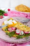 Useful french breakfast: radish salad and arugula, egg poached on a thin crape Royalty Free Stock Photos