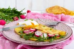Useful french breakfast: radish salad and arugula, egg poached on a thin crape Stock Photo